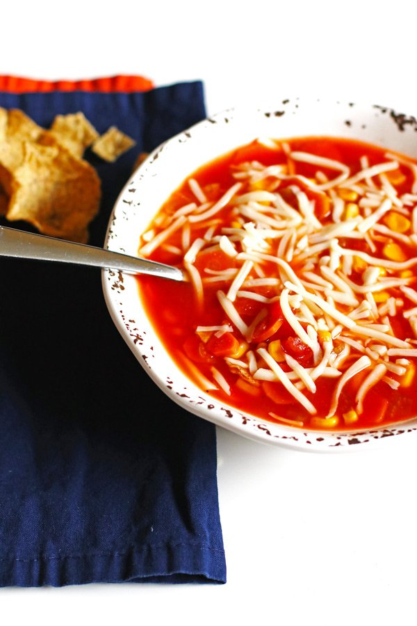 A bowl of soup with shredded mozzarella cheese over the top of it.