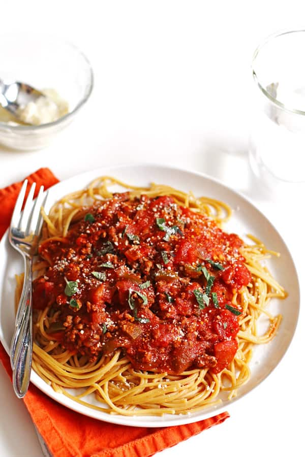 Spaghetti sauce and noodles on a white plate with a fork. A small bowl of grated parmesan cheese with a spoon is next to it.