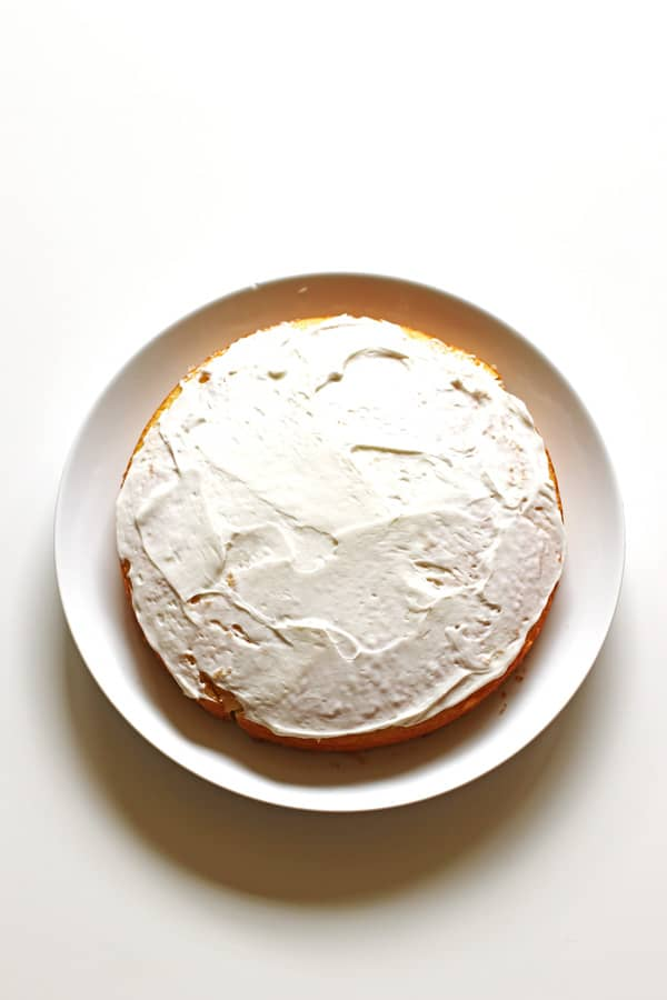 Bottom layer of cake frosted on a white serving plate