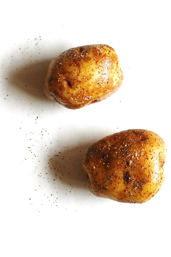 Potatoes rubbed with olive oil and sprinkled with salt and pepper on a white counter