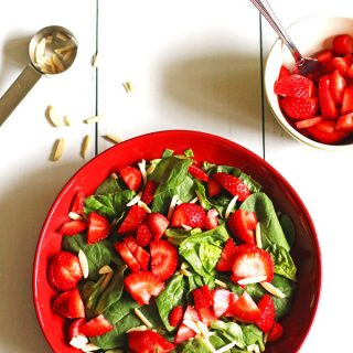 Spinach, slivered almonds and sliced strawberries in a red serving dish