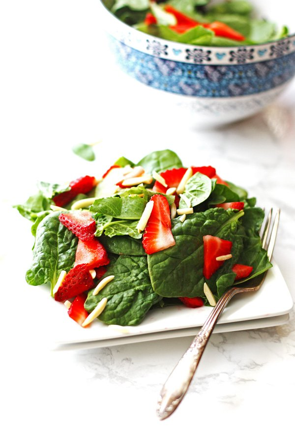 Spinach Strawberry Salad served on a white plate with a fork