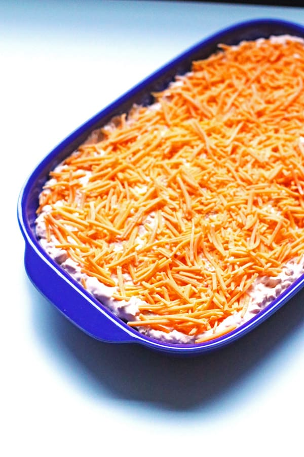 Buffalo Chicken Dip prepared and in a blue dish before baking it