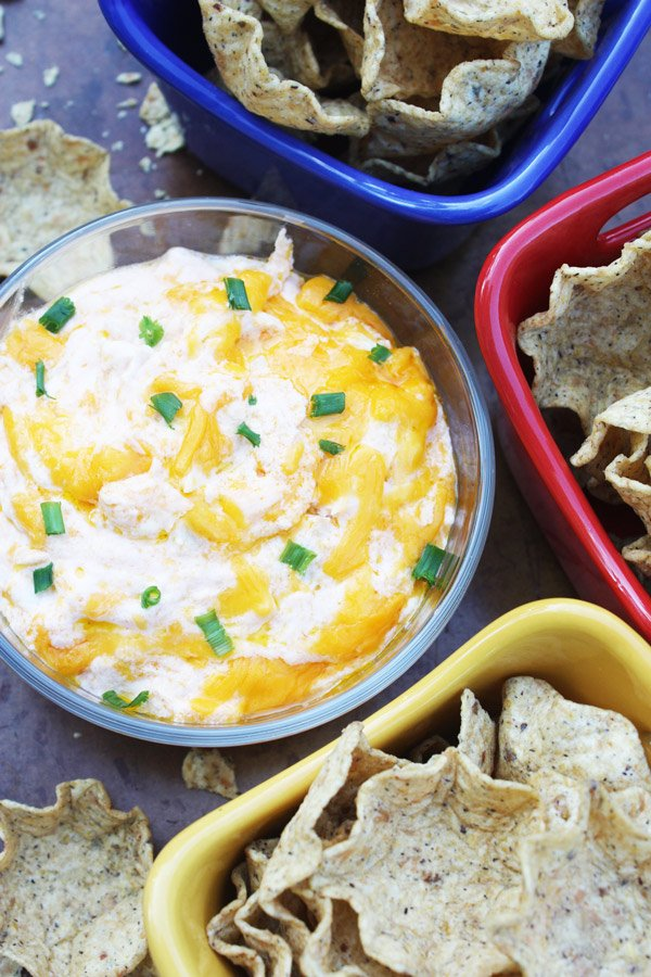 Buffalo Chicken Dip in a dish with tortilla chips in colorful dishes