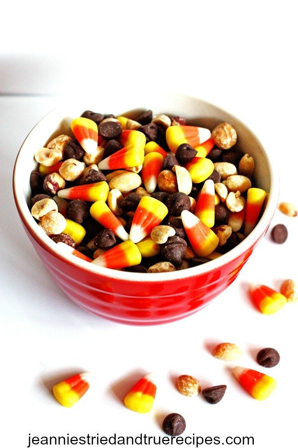 Candy corn, chocolate chips and peanuts mixed together in a bowl