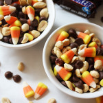 A mix of candy corn, peanuts and chocolate chips in a bowl.