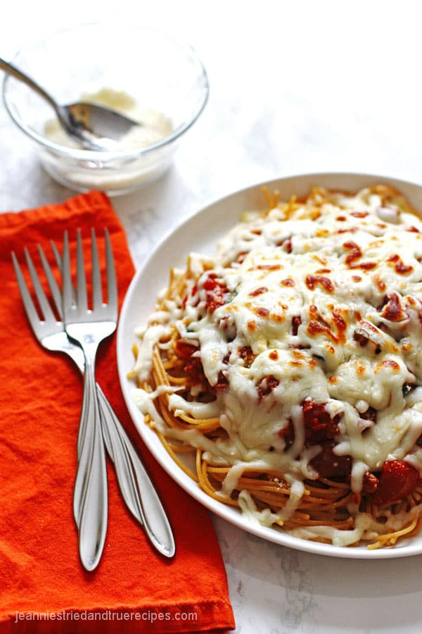 Spaghetti noodles covered in sauce and melted mozzarella cheese on a white plate