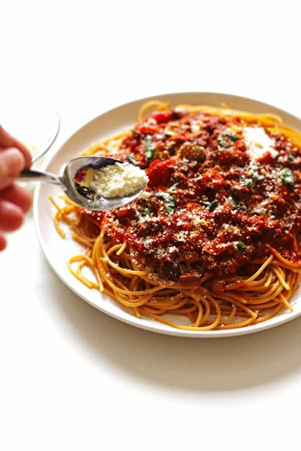 Sprinkling grated Parmesan cheese over a plate full of spaghetti noodles and sauce.