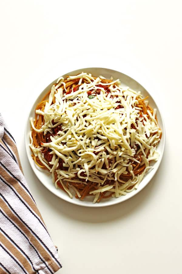 Spaghetti noodles and meat sauce covered with shredded mozzarella sauce on a white plate