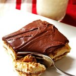 Slice of eclair cake on a plate with a glass of milk
