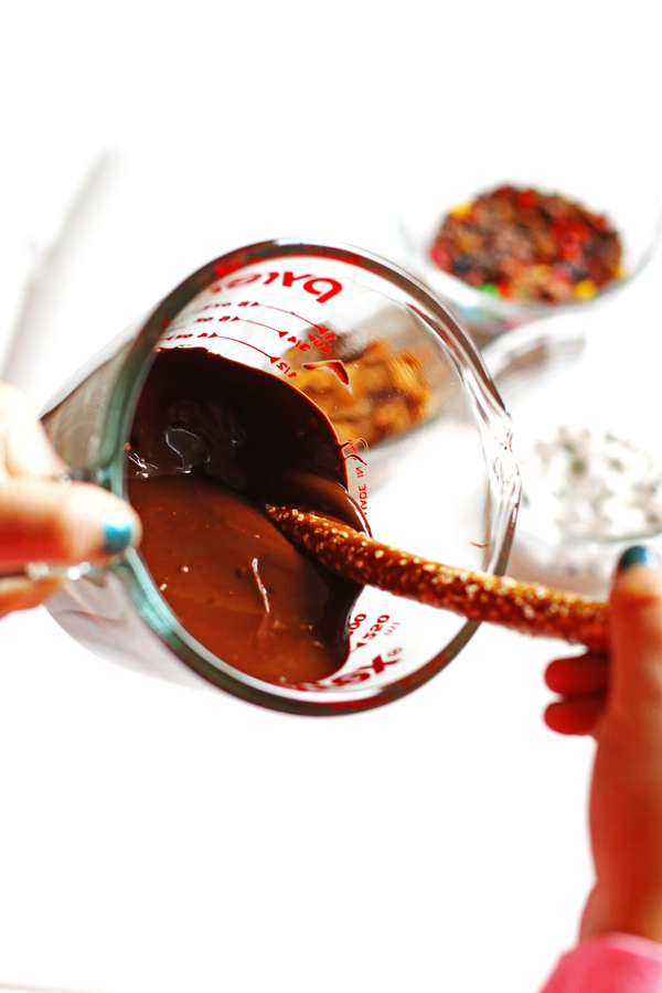 Dipping pretzel rods in melted chocolate to make Halloween Pretzel Rods