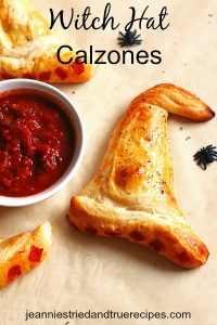 Witch Hat Calzones with a side dish of sauce on table