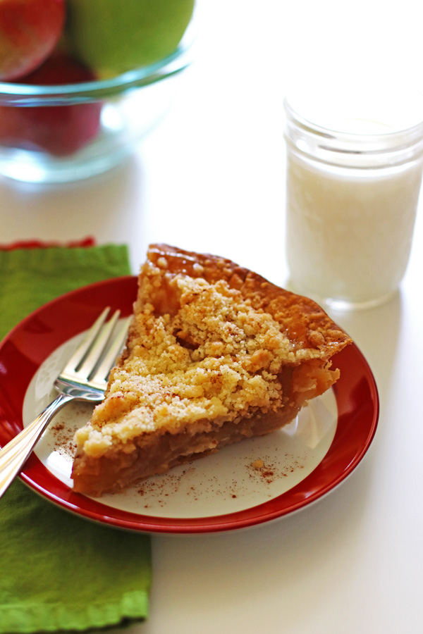 Slice of apple pie on a plate with a glass of milk