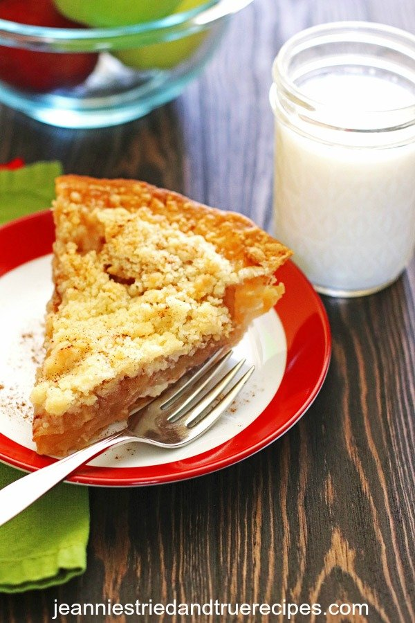 A slice of Dutch Apple Pie on a plate with a glass of milk next to it.