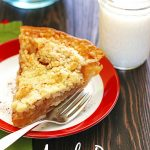 Slice of apple pie on a plate with a glass of milk.
