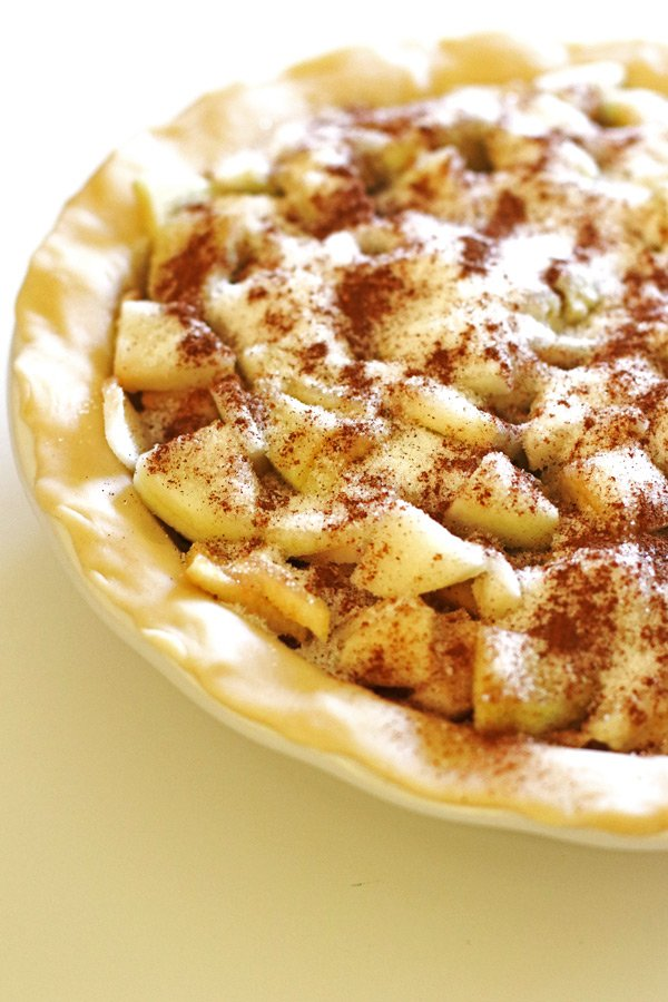 Sliced apples in pie crust with sugar and spices sprinkled over them