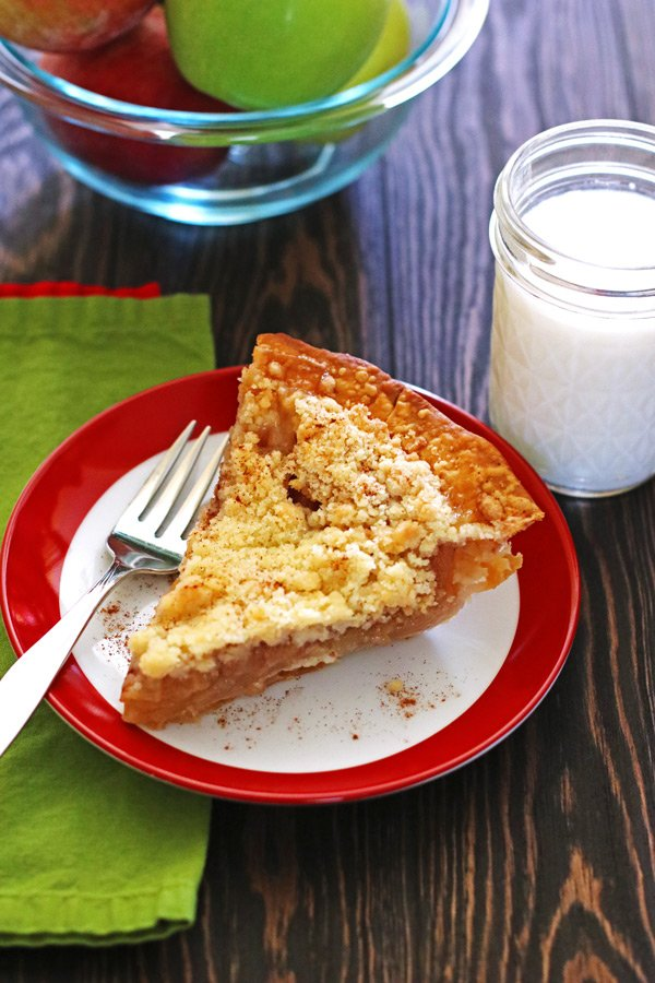 Slice of apple pie on a plate with a fork