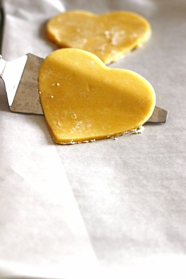 Easy Sugar Cookie dough in the shape of a heart. Using a thin pie server to pick up the cookie and place it on the baking sheet before baking.