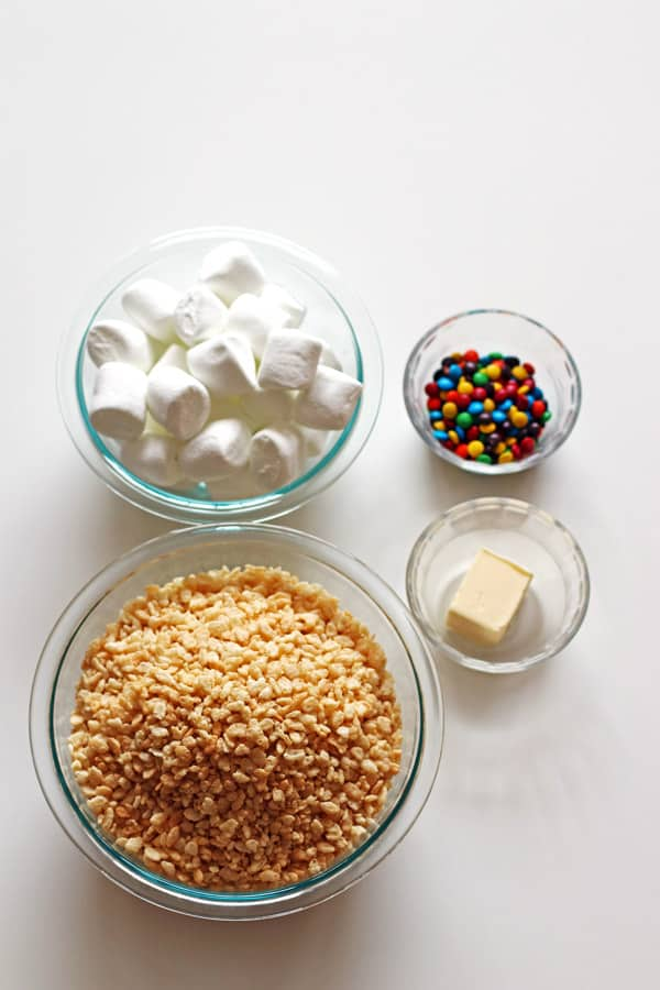 Rice Krispie cereal, marshmallows, M&M candy and butter in four separate clear bowls