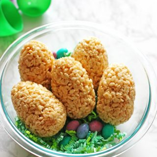Easter eggs made out of rice krispie treats and filled with M&M's placed in a clear bowl with green easter grass and candy