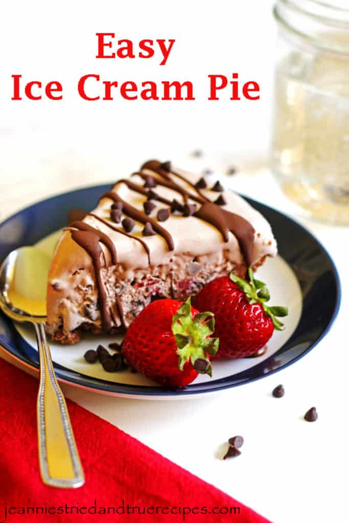 A slice of ice cream pie on a blue rimmed plate. The pie is garnished with chocolate chips, chocolate sauce and strawberries.