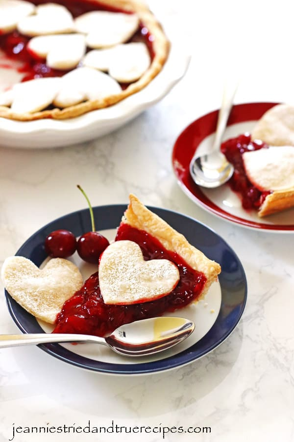 Cherry Pie slices on red and blue rimmed plates with spoons. Pie in dish next to the plates.