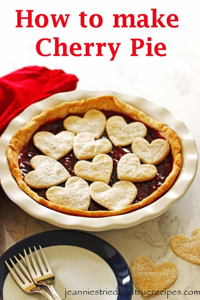 Cherry Pie in a white pie dish with cut out hearts on top sprinkled with powdered sugar