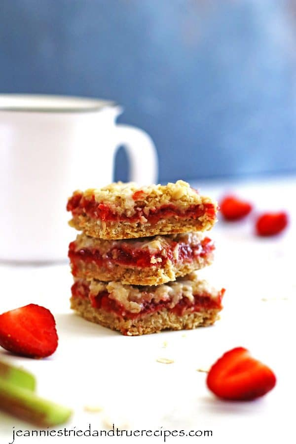 Bars made of strawberries and rhubarb cut into squares. There are three bars stacked on each other next to a white mug.