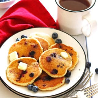 Blueberry Pancakes on a white plate with a mug filled with coffee and extra blueberries near the plate
