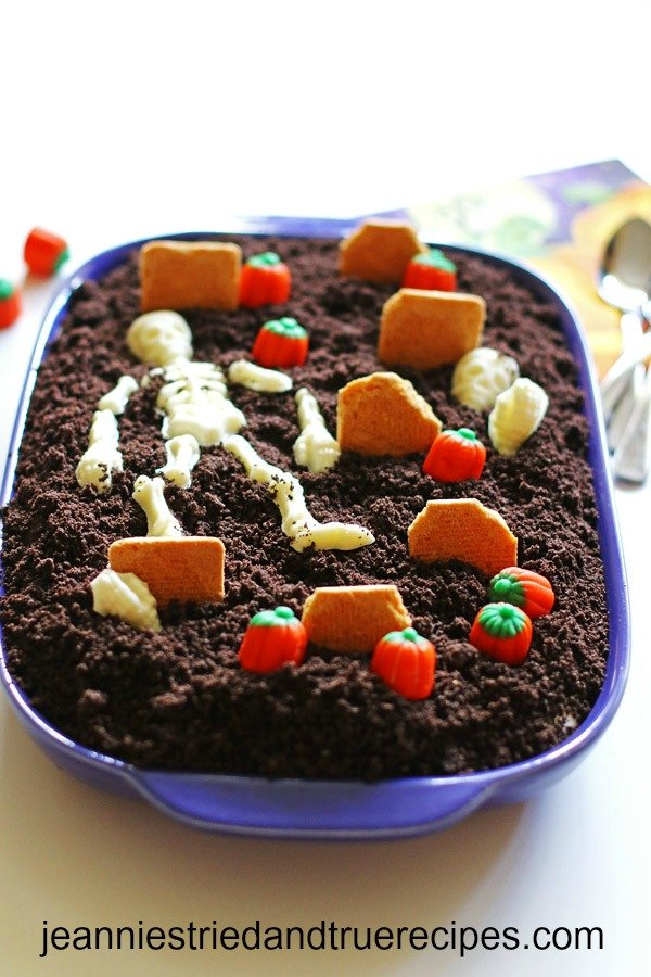 Dirt cake in a purple baking dish decorated as a graveyard. There is a candy skeleton, cookie tombstones and a candy skeleton on top of the cake.