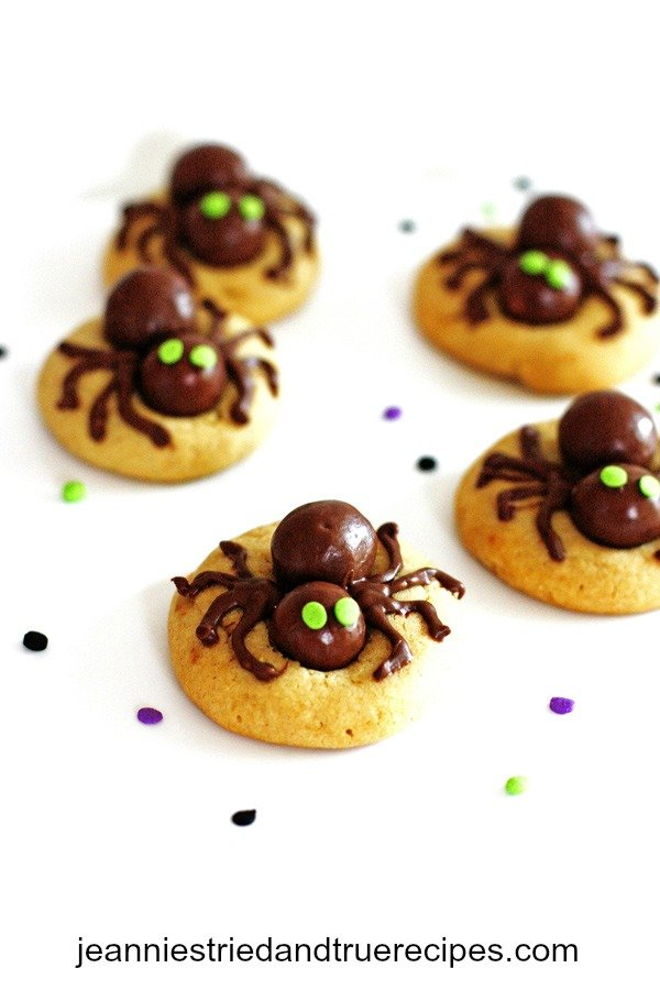 Peanut butter cookies with edible spiders on top of them