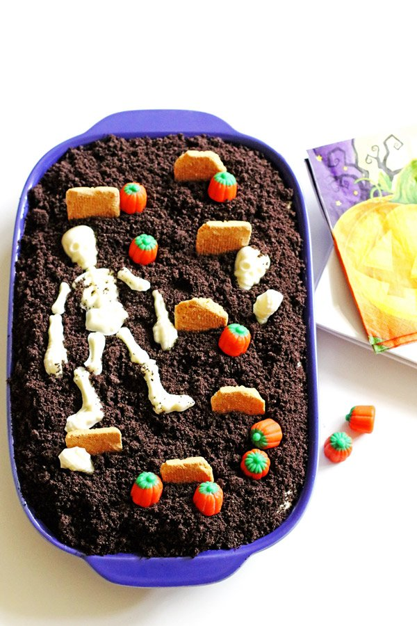 Dirt Cake decorated as a graveyard with candy pumpkins, candy skeleton and cookies as tombstones