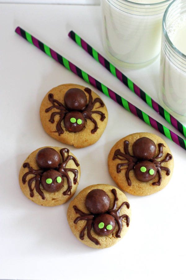 Halloween Cookies decorated with spiders on a white table with a glass of milk and two colorful straws