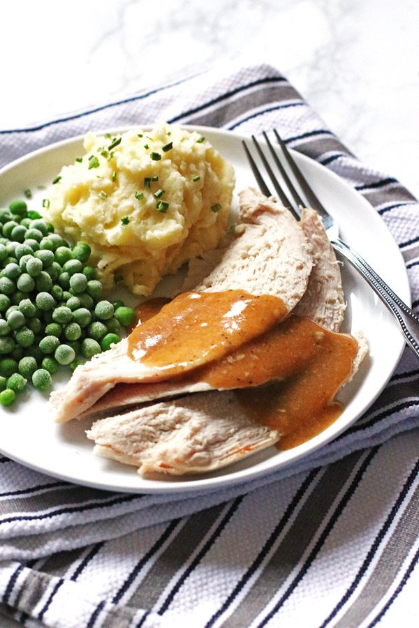 Sliced turkey, potatoes and peas on a white plate with a fork