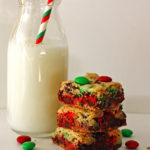 M&M Cookie Bars stacked with a glass of milk next to them