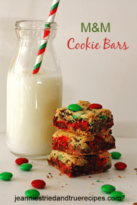 Cookie Bras made with chocolate chips and M&M's stacked next to a glass of milk