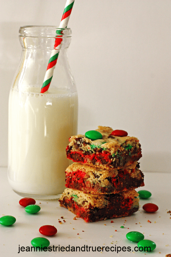 M&M Cookie Bars stacked next to a glass of milk