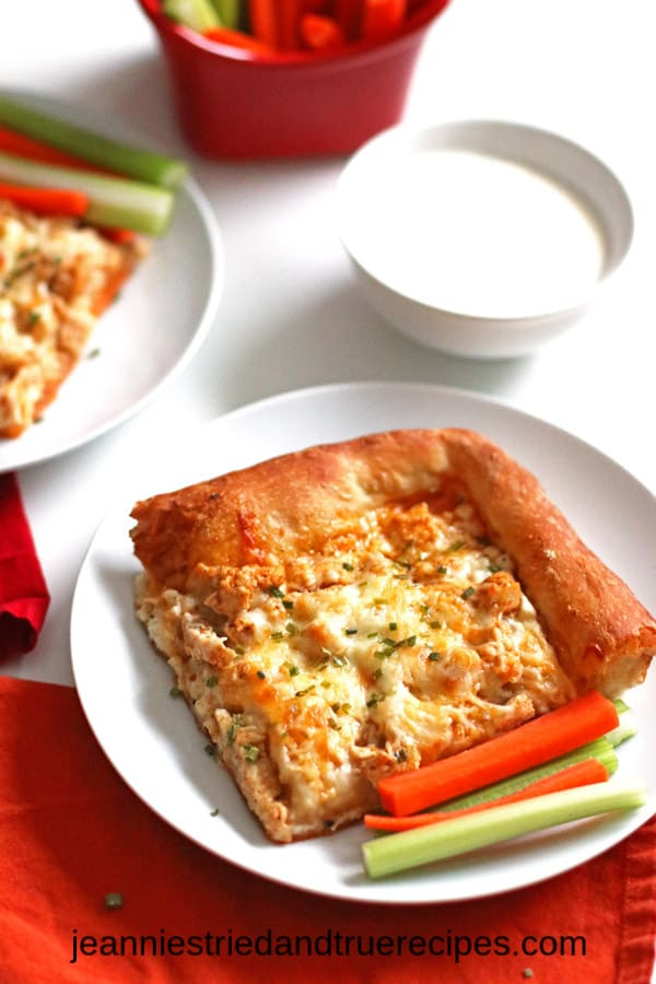 Slice of Buffalo Chicken Pizza on a white plate with carrots and celery