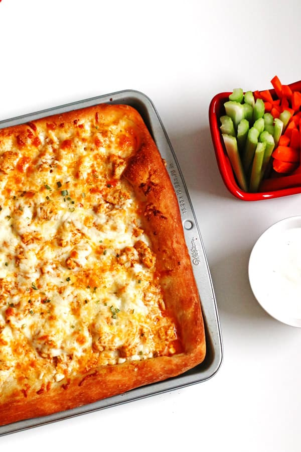 Buffalo Chicken Pizza in baking pan with carrots, celery and blue cheese dressing on the side
