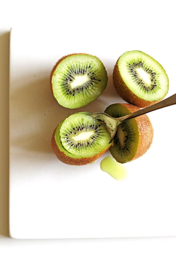Scooping out the green kiwi using a spoon