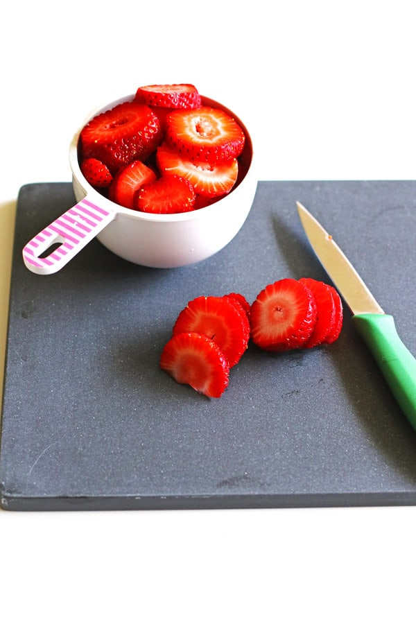 Sliced strawberries in a measuring cup sitting on a black cutting board with a knife