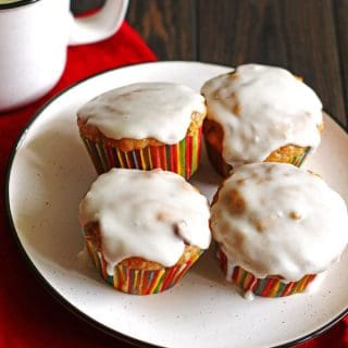 Four carrot cake muffins on a white plate with a red napkin and mug with milk next to the plate