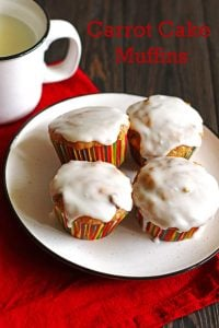 Four Carrot Cake Muffins on a white plate with a red napkin and white mug with milk