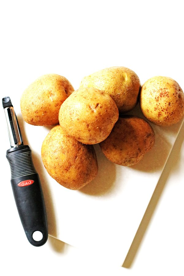 Potatoes on cutting board with a peeler