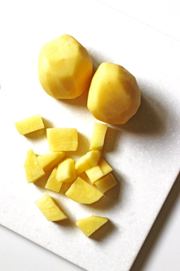 Potatoes sliced on cutting board