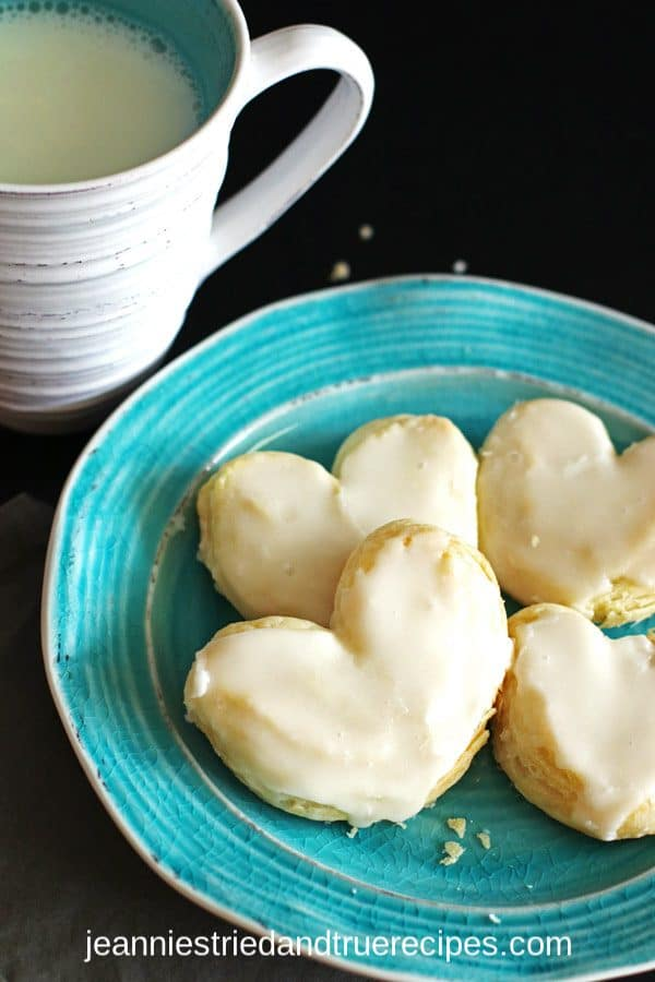 Frosted puff pastry hearts on a turquoise plate with a glass of milk