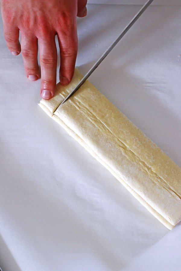Slicing the puff pastry into one inch slices with a sharp knife