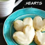 Four Puff pastry in the shape of hearts on a light blue plate with a mug of milk next to it