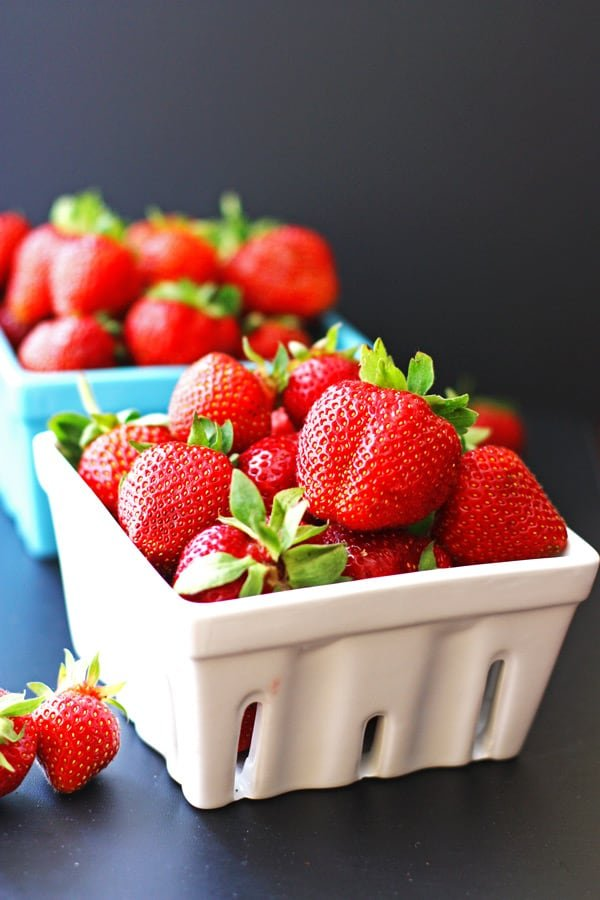 Strawberries in white and blue quart containers