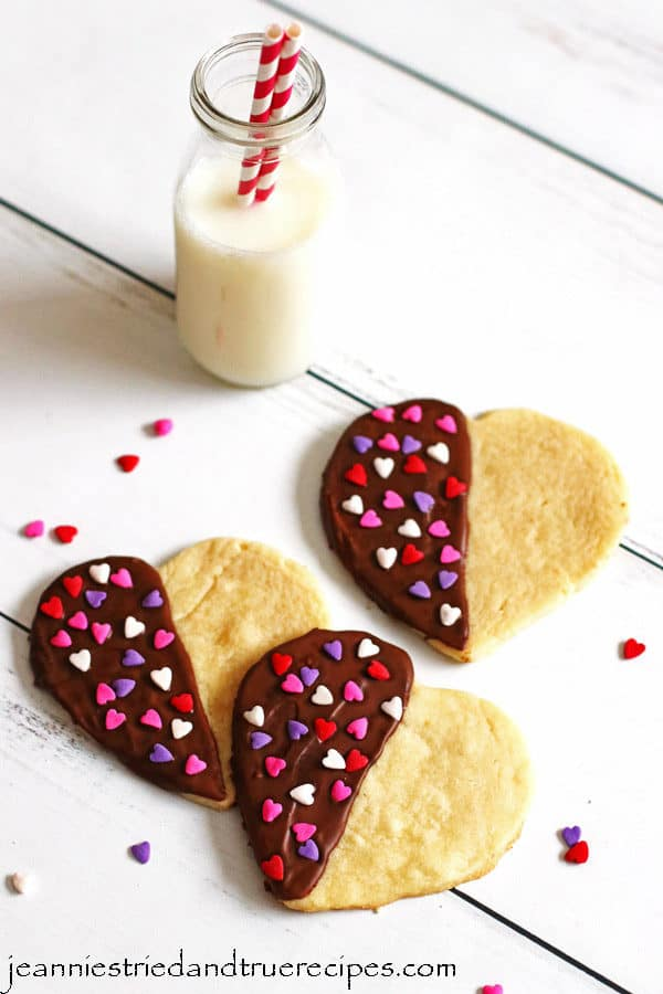 Sugar Cookies made in the shape of hearts that are half dipped in chocolate. They have red, white and pink heart sprinkles on them and are sitting on a table with a glass of milk.